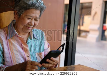 Elder Woman Holding Mobile Phone In Garden. Elderly Female Texting Message, Using App With Smartphon
