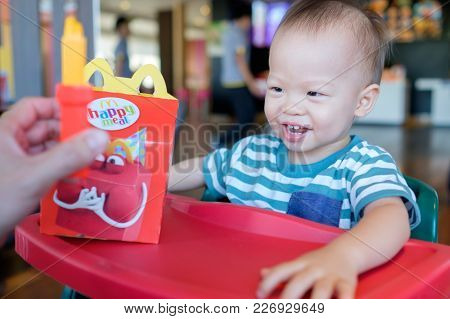 Bangkok, Thailand - October 21, 2017: Cute Little Asian Toddler Boy Sitting In High Chair Eating Hap