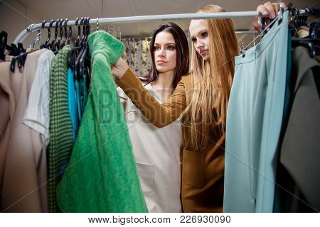Two Women Shopping Choosing Dresses. Beautiful Young Shoppers In Clothing Store.shopping Concept. Sa