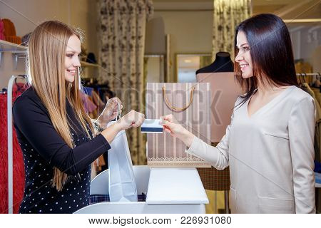 Portrait Of Pretty Woman Giving Credit Card To Shop Assistant While Paying For Her Purchase