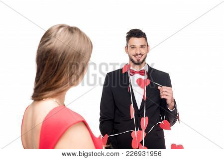Girlfriend Standing Near Happy Boyfriend Bound With Garland Of Hearts Isolated On White, Valentines