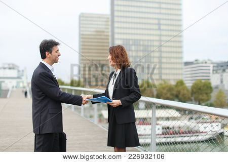 Man With Smartphone Going Towards Woman With Blue Folder Of Documents, Old It Business Partners Meet