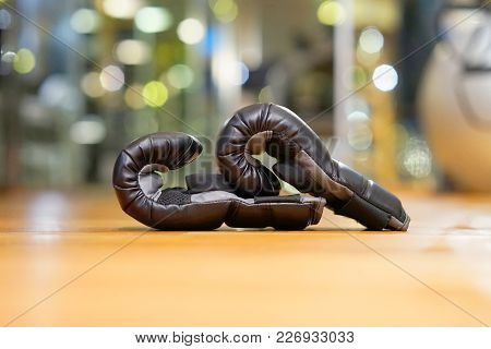 Black Boxing Gloves On The Floor Of The Gym. Concept Of Strength And Sport.