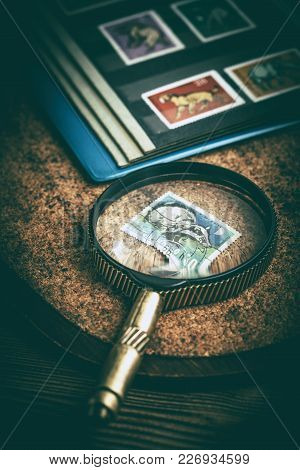 Book With Postage Stamps And A Magnifying Glass.