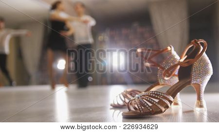 Blurred Professional Man And Woman Dancing Latin Dance In Costumes In The Studio, Ballroom Shoes In