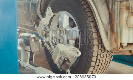Car In Auto Service Lifting For Repairing, Mechanics In Garage, Close Up
