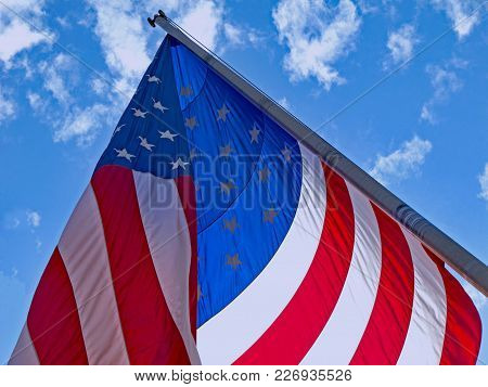 A Large Sunlit Flag Of The United States Of America Flies In The Breeze.
