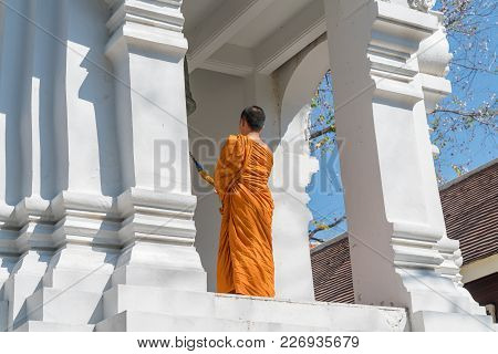 Chiang Mai Thailand - January 29 2018; Buddhist Monk In Orange Robes Stands  On High Level Of White
