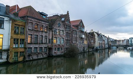Ghent, Belgium - February 2018: Picturesque Medieval Buildings Overlooking The Graslei Harbor On Lei