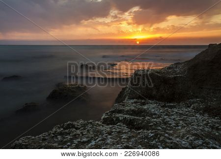 A Long Exposure Of Dramatic Sunset Over The Sea, With Rocky Seashore