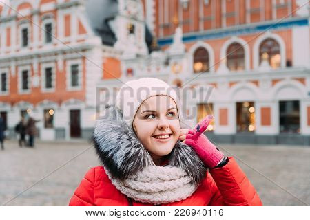 Riga, Latvia. Young Beautiful Pretty Caucasian Girl Woman Dressed In Red Jacket And White Hat Enjoyi