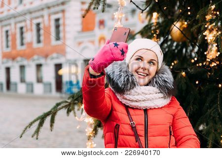 Riga, Latvia. Young Beautiful Pretty Caucasian Girl Woman Dressed In Red Jacket And White Hat Having