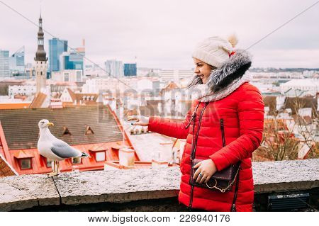 Tallinn, Estonia. Young Beautiful Pretty Caucasian Girl Woman Dressed In Red Jacket And White Hat Be