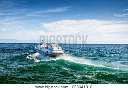 White Ferryboat On Blue See With Splashes In The Sunny Day