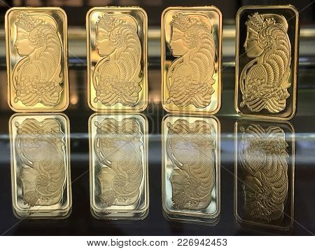 Gold Bullion And Gold Investment Bars On Glass