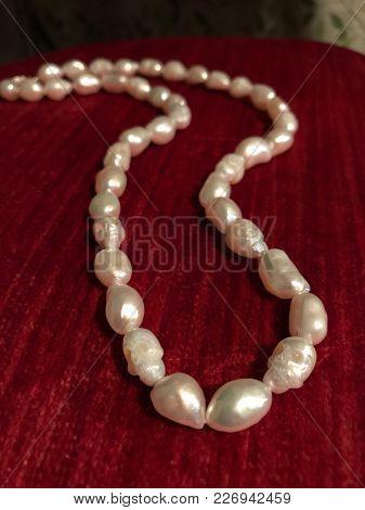 Carved Skull Pearl Necklace On Red Velvet Background