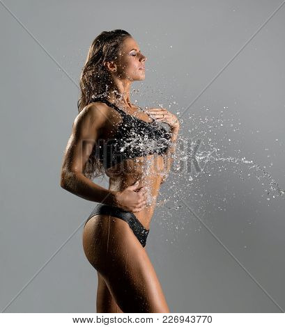 Beautiful Woman In Sexy Black Top And Shorts Enjoying Shower Cropped View On Gray Background