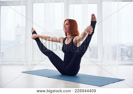 Beautiful Young Red Head Woman Practices Yoga Asana Urdhva Upavistha Konasana At The Yoga Studio