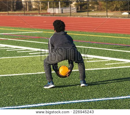 A High School Track And Field Athlete Is Squatting Down Ready To Throw A Medicine Ball Over His Head