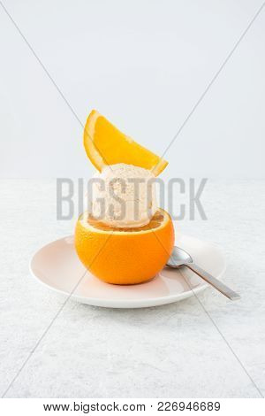 Scoop Of Homemade Orange Ice Cream Served On An Orange And Decorated With An Orange Slice.