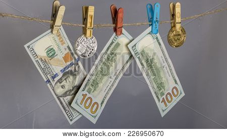 Money Laundering Concept. Yellow Clothes Peg Hold Bitcoin And One Hundred Dollar Banknotes.