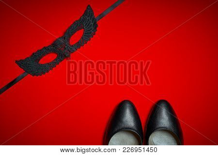 Top View Of A Sexy Black Mask And High Heels On A Red Intense Background