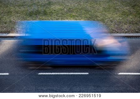 Blue Delivery Van Driving Very Quickly Causing A Significant Motion Blur Effect