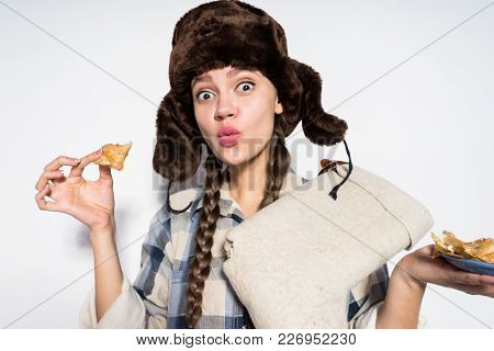 A Funny Russian Girl In A Cap With Earflaps Celebrates Carnival, Eats Delicious Hot Pancakes