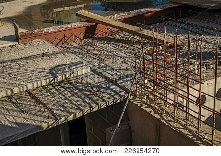 Close-up Of Concrete Floor And Steel Bars In A Construction Area At Sunset In Tielt. Charming And Qu