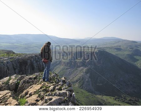 Woman Standing On Edge Of A Cliff, Looking Down Toward A Valley In The Arbel Cliff, Israel
