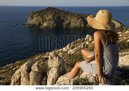 A Woman On Vacation With Straw Hat Is Sitting On Rock,holding A Book At Her Laps And Looking At The
