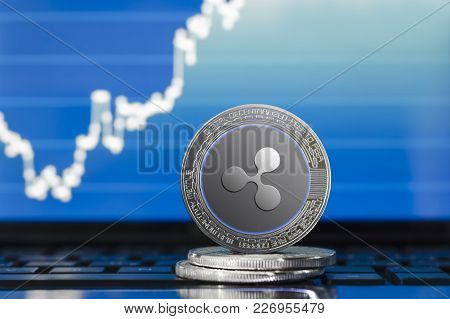 Physical Ripple (xrp) Cryptocurrency; Silver Ripple Coin On The Background Of The Chart