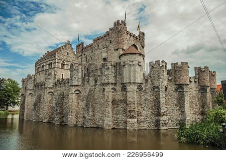 Lake And Stone Wall In Front Of Gravensteen Castle On Cloudy Day In Ghent. In Addition To Intense Cu