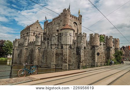 Bridge And Bike In Front Of Gravensteen Castle On Cloudy Day In Ghent. In Addition To Intense Cultur
