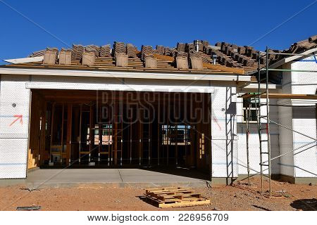 A Garage And Home Under Construction With Scaffolding And Tile  Shingles On The Roof.