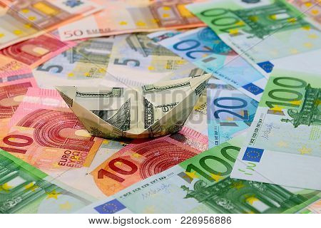 a boat folded from a bill hundred dollars against the background of the euro