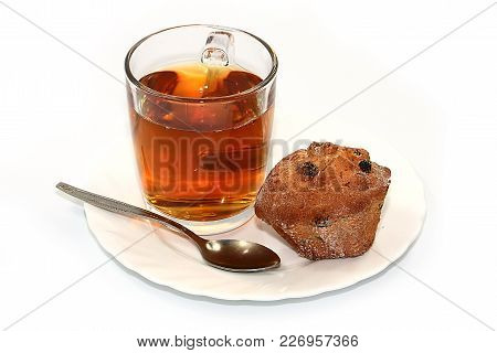 a cup of hot strong black tea and a cupcake on a plate