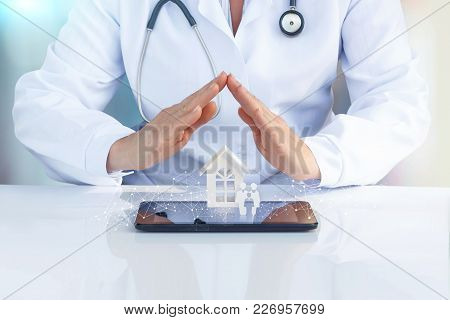 Doctor At The Table With His Hands To Protect The Icon The Family And Home. The Concept Of Health In