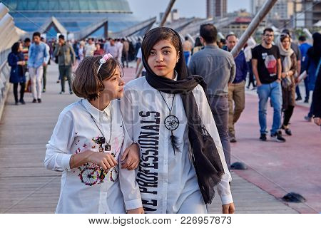 Tehran, Iran - April 28, 2017: Two Girls Are Walking Along The Tabiat Bridge In A Crowd Of Other Peo