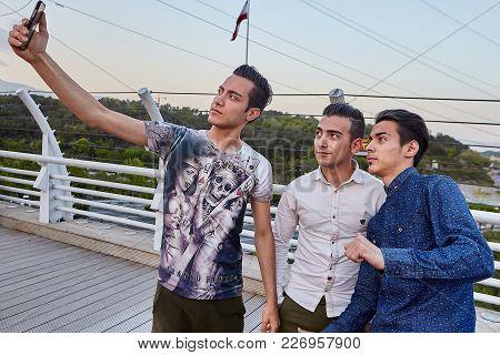 Tehran, Iran - April 28, 2017: Three Iranian Young Men Make Selfies On Tabiat Bridge, Using A Mobile
