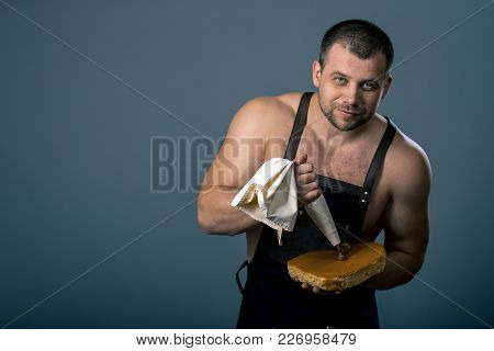 Confectioner Is Decorating Chocolate Cake. Chef Chewing Chocolate Cream On Cake On Dark Background A
