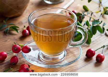 A Cup Of Rose Hip Tea With Fresh Rose Hips On A Wooden Table