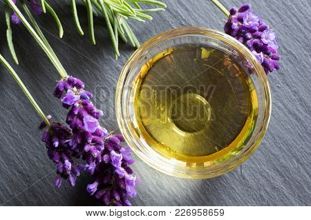 Lavender Essential Oil In A Glass Bowl With Fresh Lavender Twigs, Top View