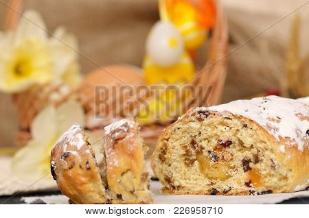Sweet Easter bread with marzipan, candied fruits, nuts, dried fruits. Holland traditional Easter bread paasbrood. Easter basket with Easter eggs on background. Easter cake. Easter paasbrood. Easter bakery.