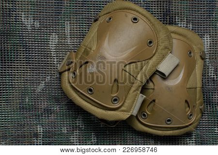 Old Pair Of  Tactical Knee Pads Lies On A Multicam Background.