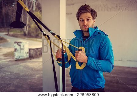 A Man In A Park Improving His Legs Flexibility With Fitness Trx Strips.