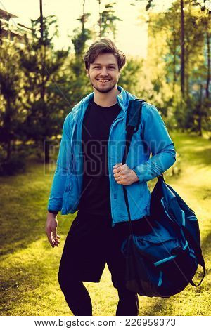 A Man In A Blue Sports Jacket With Sports Bag Posing In A Park.