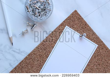 White Marble Desk With Silver Push Pins, Pencil And Note On Cork Board. Copy Space.
