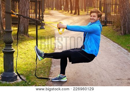Attractive Positive Male In A Blue Raincoat Exercising In A Park With Trx Fitness Strips.