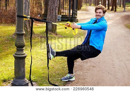 Attractive Positive Male Exercising With Trx Fitness Strips.